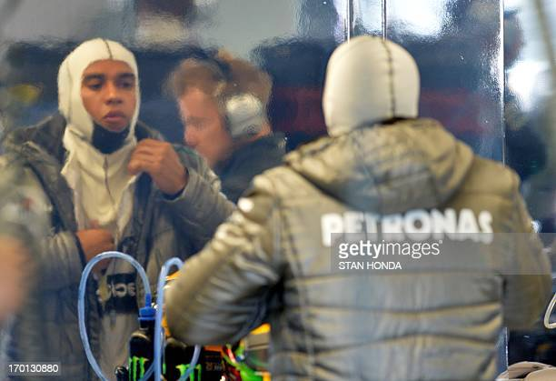 Mercedes driver Lewis Hamilton looks into a mirrored wall as he puts on his suit in the pits during practice at the Canadian Formula One Grand Prix...