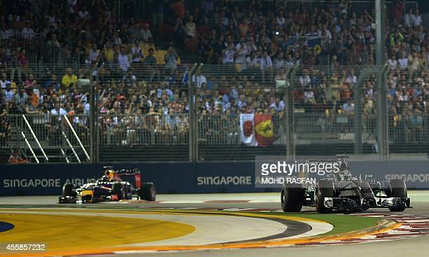 Mercedes driver Lewis Hamilton of Britain and Red Bull Racing driver Daniel Ricciardo of Australia drive during the the Formula One Singapore Grand...