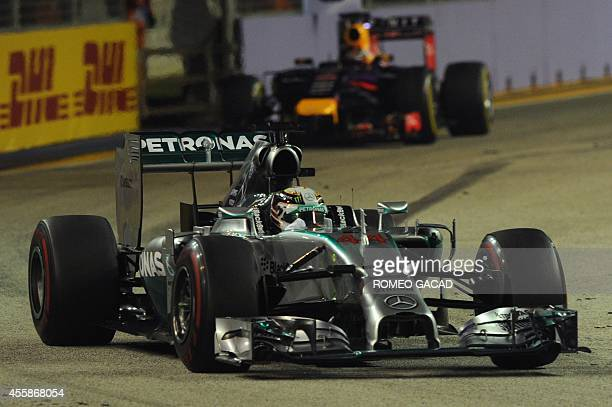 Mercedes driver Lewis Hamilton of Britain drives ahead of Red Bull Racing driver Sebastian Vettel of Germany seen in the background during the...