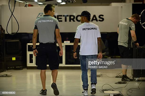 Mercedes driver Lewis Hamilton of Britain talks to a team officer at the pit area of the Formula One Singapore Grand Prix on September 18 2014 The...