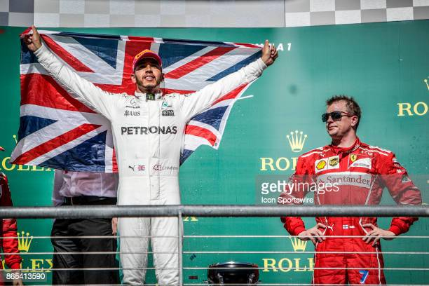 Mercedes driver Lewis Hamilton of Great Britain holds flag of Great Britain as Ferrari driver Kimi Raikkonen of Finland looks on after the Formula 1...