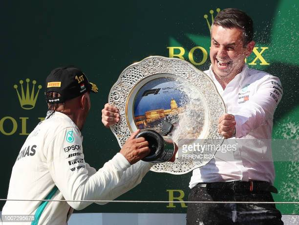 Mercedes' engineer Riccardo Musconi and Mercedes' British driver Lewis Hamilton celebrate on the podium after winning the Formula One Hungarian Grand...