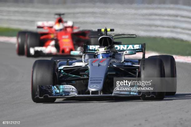 Mercedes' Finnish driver Valtteri Bottas and Ferrari's German driver Sebastian Vettel compete in the Formula One Russian Grand Prix at the Sochi...