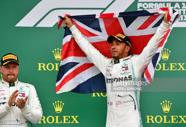 Mercedes' Finnish driver Valtteri Bottas applauds as Mercedes' British driver Lewis Hamilton holds up the Union flag on the podium as he celebrates...