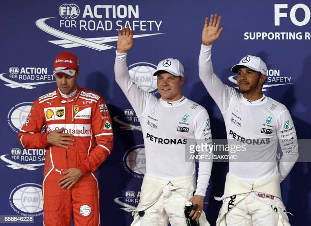 Mercedes' Finnish driver Valtteri Bottas celebrates after taking the pole position next to his teammate Lewis Hamilton and Ferrari's German driver...