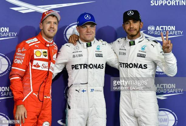 Mercedes' Finnish driver Valtteri Bottas celebrates after taking the pole position followed by Mercedes' British driver Lewis Hamilton and Ferrari's...