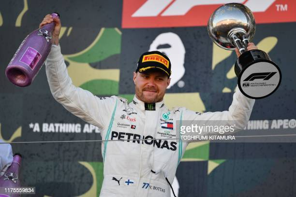 TOPSHOT Mercedes' Finnish driver Valtteri Bottas celebrates his victory on the podium after the finish of the Formula One Japanese Grand Prix final...