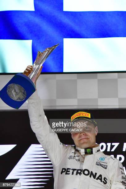 Mercedes' Finnish driver Valtteri Bottas celebrates on the podium at the end of the Abu Dhabi Formula One Grand Prix at the Yas Marina circuit on...