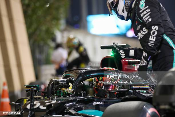 Mercedes' Finnish driver Valtteri Bottas congratulates his teammate, Mercedes' British driver George Russell, after the qualifying session ahead of...