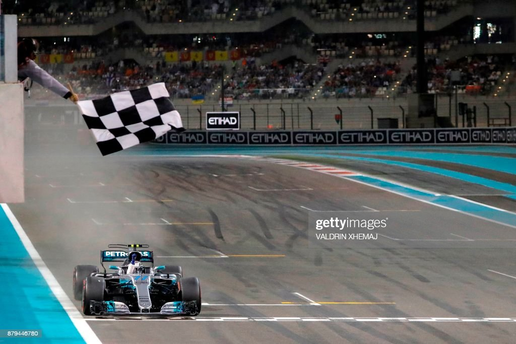 Mercedes' Finnish driver Valtteri Bottas crosses the finish line during the Abu Dhabi Formula One Grand Prix at the Yas Marina circuit on November 26, 2017. /