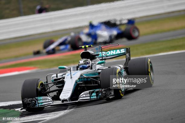 Mercedes' Finnish driver Valtteri Bottas drives ahead Sauber's Swedish driver Marcus Ericsson during the third practice session at the Silverstone...