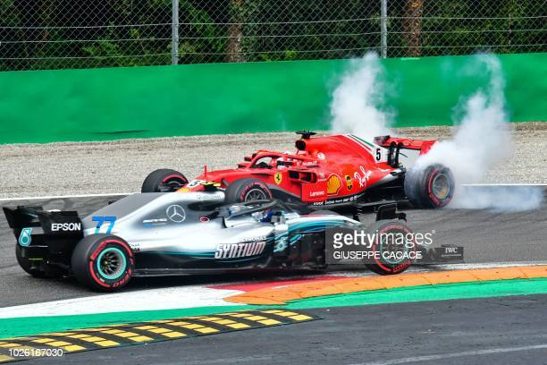 TOPSHOT Mercedes' Finnish driver Valtteri Bottas drives past Ferrari's German driver Sebastian Vettel's car after Vettel crashed with Mercedes'...