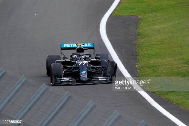 Mercedes' Finnish driver Valtteri Bottas drives with a puncture during the Formula One British Grand Prix at the Silverstone motor racing circuit in...