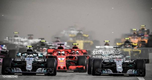 Mercedes' Finnish driver Valtteri Bottas , Ferrari's German driver Sebastian Vettel and Mercedes' British driver Lewis Hamilton steer their cars...