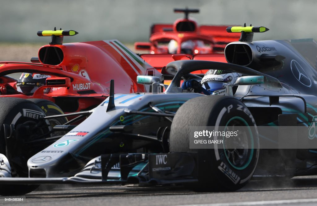 Mercedes Finnish driver Valtteri Bottas (front) fights for position with Ferrari's Finnish driver Kimi Raikkonen (L) and Ferrari's German driver Sebastian Vettel (rear) during the Formula One Chinese Grand Prix in Shanghai on April 15, 2018. /