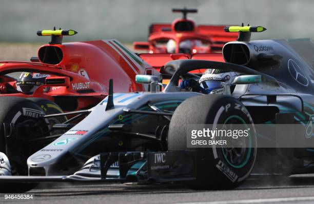 Mercedes Finnish driver Valtteri Bottas fights for position with Ferrari's Finnish driver Kimi Raikkonen and Ferrari's German driver Sebastian Vettel...