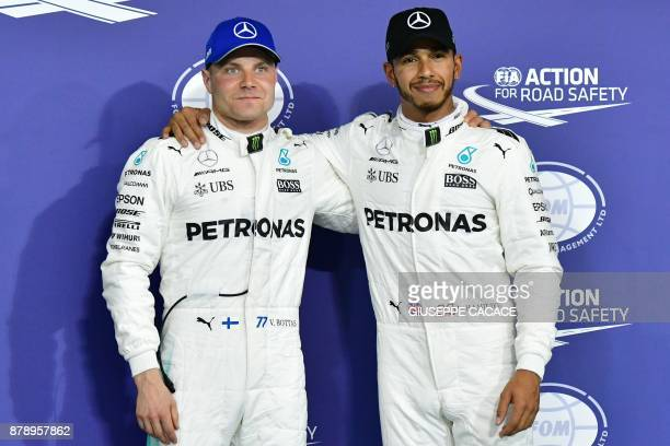 Mercedes' Finnish driver Valtteri Bottas poses with his teammate British driver Lewis Hamilton at the end of the qualifying session ahead of the Abu...