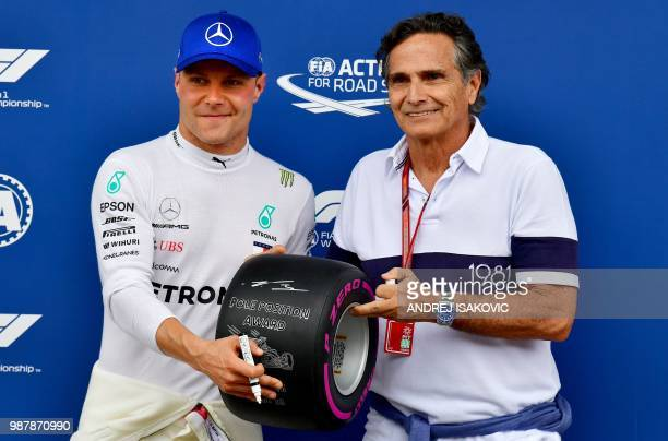Mercedes' Finnish driver Valtteri Bottas receives the pole position award by former Brazilian racing legend Nelson Piquet after the qualifying ahead...