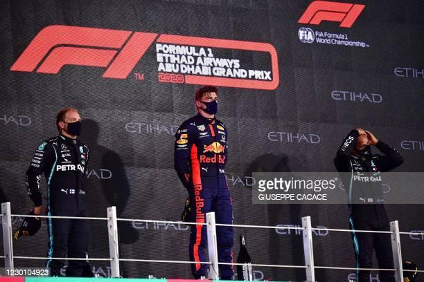 Mercedes' Finnish driver Valtteri Bottas , Red Bull's Dutch driver Max Verstappen and Mercedes' British driver Lewis Hamilton stand on the podium...