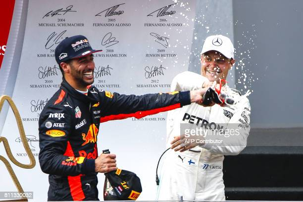 Mercedes' Finnish driver Valtteri Bottas refuses the 'shoey' of Red Bull's Australian driver Daniel Ricciardo as they celebrate on the podium after...