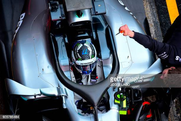 TOPSHOT Mercedes' Finnish driver Valtteri Bottas rests in the pits at the Circuit de Catalunya on March 1 2018 in Montmelo on the outskirts of...