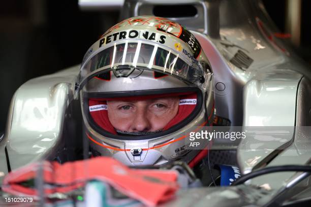 Mercedes' German driver Michael Schumacher stands in the pits with his helmet during the first practice session at the SpaFrancorchamps circuit on...