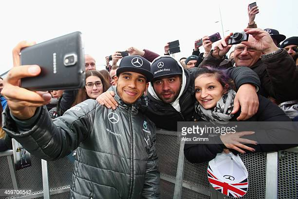 Mercedes GP Formula One driver Lewis Hamilton of Great Britain poses for a selfie with fans during the annual Mercedes Benz Stars & Cars event in...