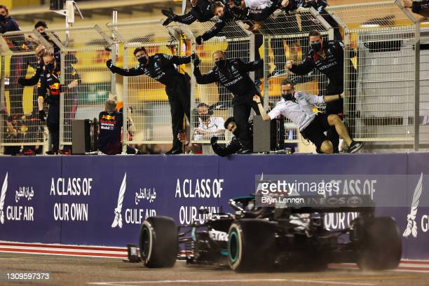 Mercedes GP team members celebrate on the pitwall as Lewis Hamilton of Great Britain driving the Mercedes AMG Petronas F1 Team Mercedes W12 crosses...