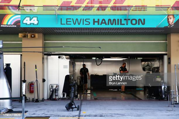 Mercedes GP team members work in the garage of Lewis Hamilton of Great Britain and Mercedes GP during previews ahead of the F1 Grand Prix of Abu...