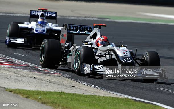 Mercedes GP's German driver Michael Schumacher drives ahead of Williams' Brazilian driver Rubens Barrichello at the Hungaroring circuit on August 01...