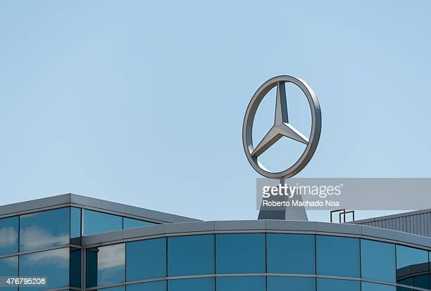 Mercedes symbol standing on the roof of a dealer with large windows over blue sky