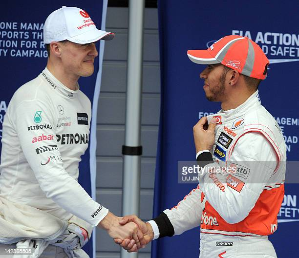 Mercedes-AMG driver Michael Schumacher of Germany shakes hands with McLaren-Mercedes driver Lewis Hamilton of Britain after the qualifing session of...