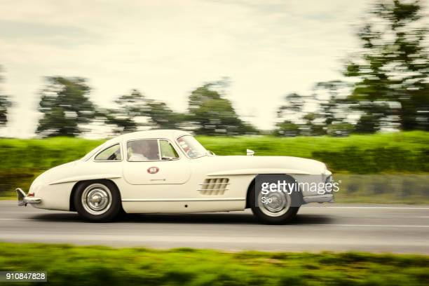 mercedes-benz 300sl gullwing classic sports car driving at high speed - mercedes benz 300sl gullwing stock photos and pictures
