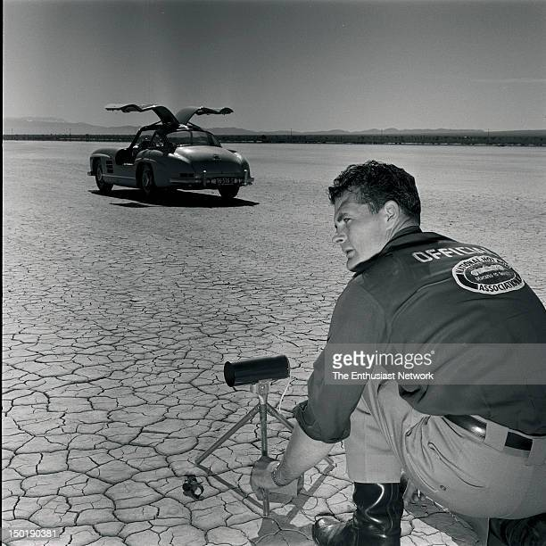 MercedesBenz 300SL Road Test An NHRA official prepares the timing lights for chronograph speed testing on the dry lake bed MB 300SL in the background...