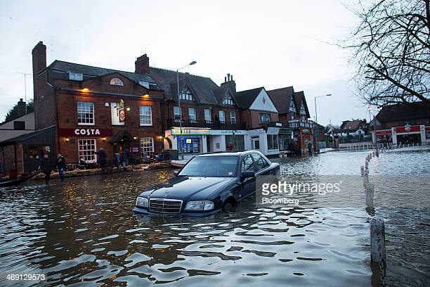 A MercedesBenz automobile sits partially submerged in flood water as a Costa Coffee shop operated by Whitbread Plc stands beyond on the high street...