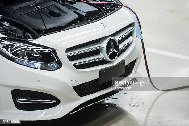 Mercedes-Benz badge sits on the grill of an automobile beneath the open bonnet and engine at the Mercedes-Benz AG automobile plant, operated by...