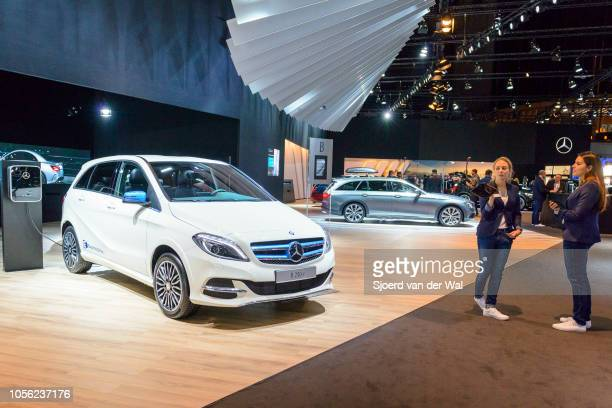 MercedesBenz Bclass B 250 e plugin hybrid with two saleswomen standing next to the compact luxury MPV car on display at Brussels Expo on January 13...