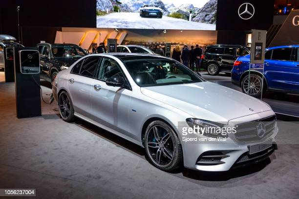 Mercedes-Benz E-class E 350 e sedan plug-in hybrid luxury car connected to an electric vehicle charging station on display at Brussels Expo on...