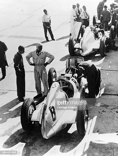 Mercedes-Benz Grand Prix car, c1934. Mechanics work on the cars, one of the drivers standing by. Mercedes was one of the dominant teams in Grand Prix...
