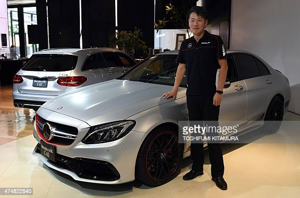 MercedesBenz Japan president and CEO Kintaro Ueno poses among the company's new MercedesAMG C63 S Edition 1 and MercedesAMG C63 S station wagon...