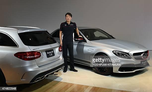 MercedesBenz Japan president and CEO Kintaro Ueno poses among the company's new MercedesAMG C63 S station wagon and MercedesAMG C63 S Edition 1...