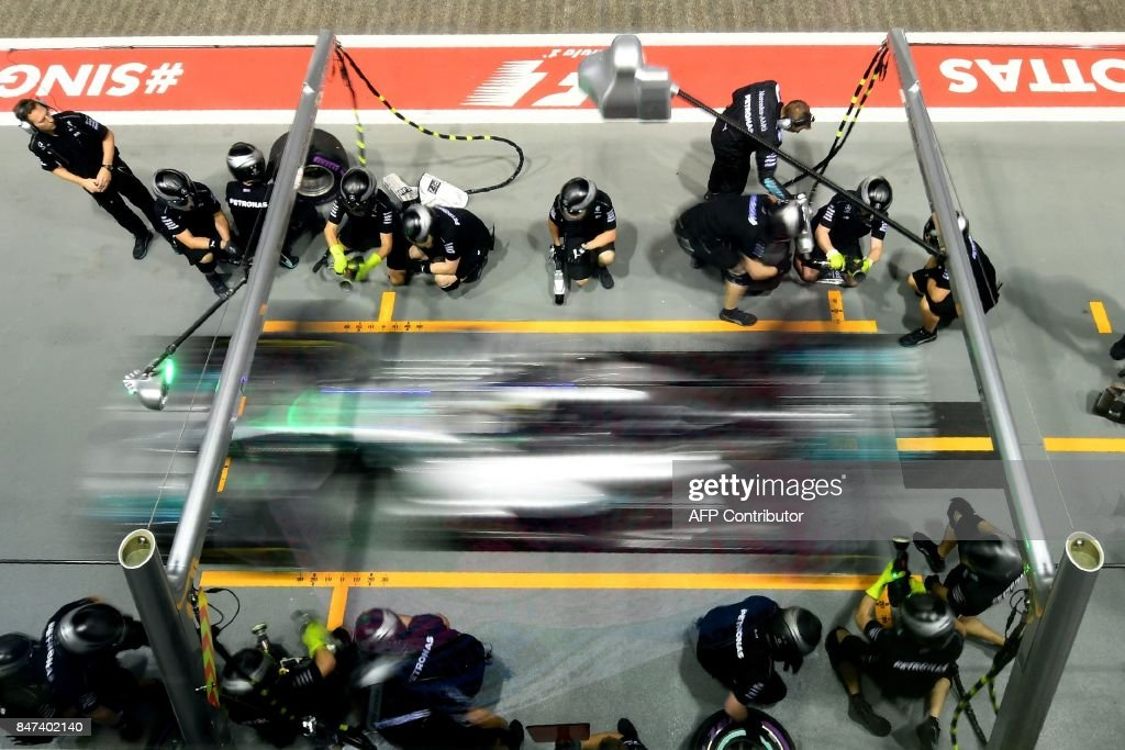 TOPSHOT - Mercedes's British driver Lewis Hamilton drives out of the pit-lane during the second practice session of the Formula One Singapore Grand Prix night race on September 15, 2017. /