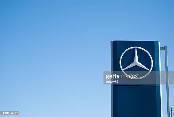mercedez-benz dealership sign against clear sky - mercedes benz stock pictures, royalty-free photos & images