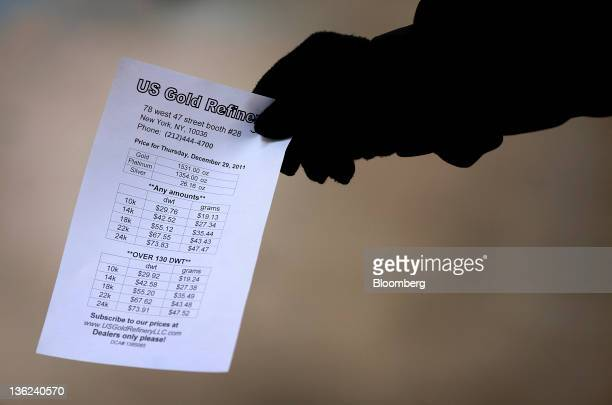 A merchant hands out a flyer listing gold prices in New York US on Thursday Dec 29 2011 Gold is poised to complete its 11th consecutive annual gain...