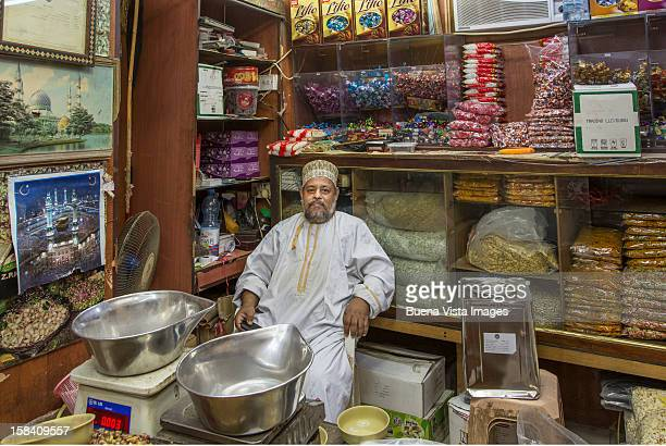 merchant in his shop in the souk of muscat. - muscat governorate stock pictures, royalty-free photos & images