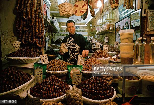 A merchant in the souq in Fes Morocco selling dates and dried goods 2004