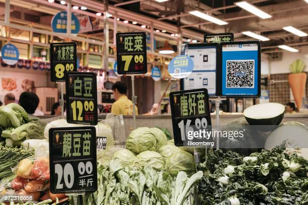 A merchant quick response code and payment instructions for Ant Financial Services Group's Alipay an affiliate of Alibaba Group Holding Ltd right are...