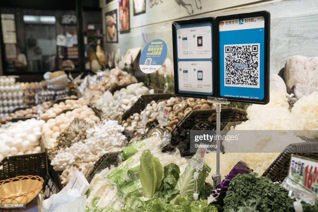 A merchant quick response (QR) code and payment instructions for Ant Financial Services Group's Alipay, an affiliate of Alibaba Group Holding Ltd., are displayed at a vegetable stall inside MC Box Po Tat Market in Hong Kong, China, on Tuesday, Nov. 7, 2017. Ant Financial, which has been valued as high as $75 billion, is the world's most valuable closely held fintech company. Photographer: Anthony Kwan/Bloomberg via Getty Images