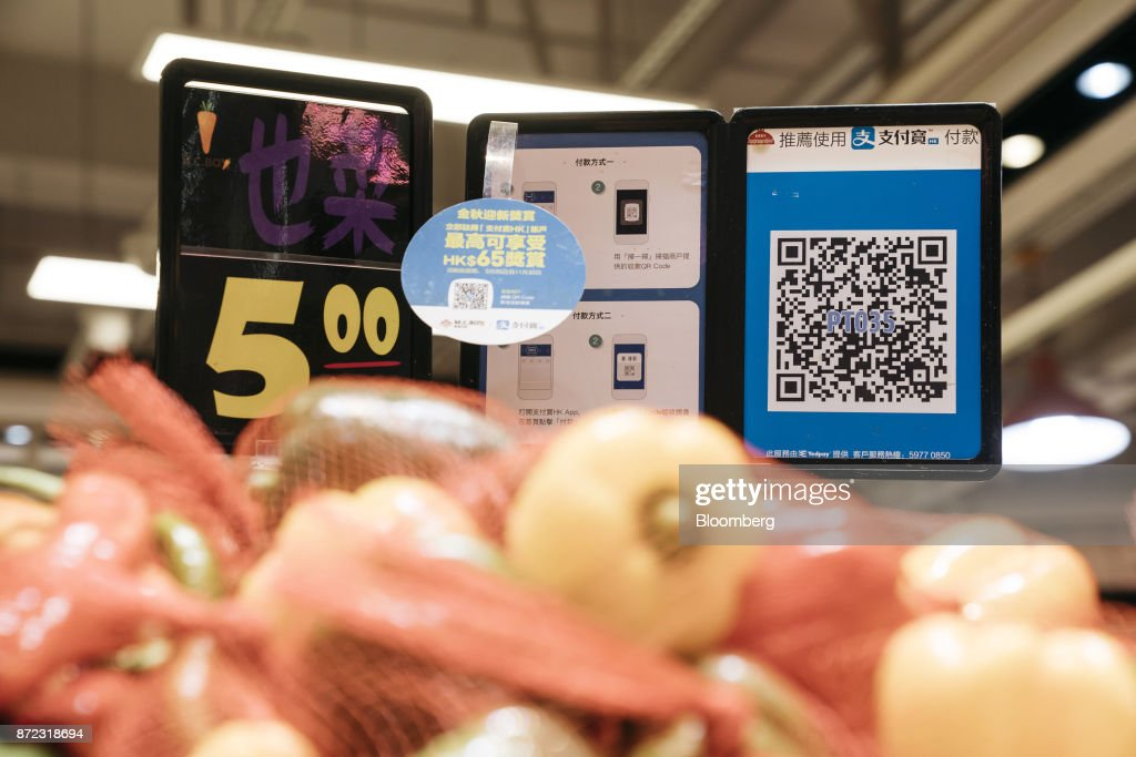 A merchant quick response (QR) code and payment instructions for Ant Financial Services Group's Alipay, an affiliate of Alibaba Group Holding Ltd., are displayed next to a price sign at a vegetable stall inside MC Box Po Tat Market in Hong Kong, China, on Tuesday, Nov. 7, 2017. Ant Financial, which has been valued as high as $75 billion, is the world's most valuable closely held fintech company. Photographer: Anthony Kwan/Bloomberg via Getty Images