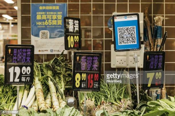 A merchant quick response code for Ant Financial Services Group's Alipay an affiliate of Alibaba Group Holding Ltd second right is displayed next to...